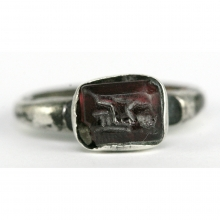 Hellenistic silver ring with garnet bezel depicting a seated Warrior