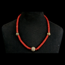 A necklace comprising natural red coral including three round Pumtek beads