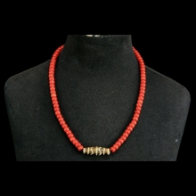 A necklace comprising natural red coral with a central Pumtek bead
