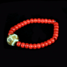 A bracelet comprising natural red coral with a central Pumtek bead