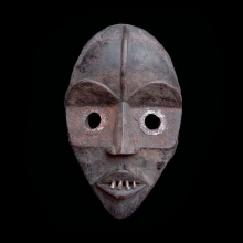 A Dan wooden mask, embellished with metal eyes and animal teeth.