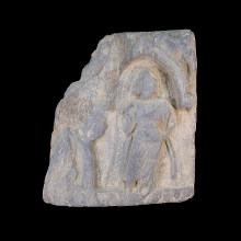 A Gandharan grey schist fragment depicting a figure standing within a Naiskos