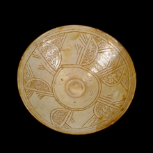 A lovely Persian cream-glazed ceramic bowl with incised decoration.
