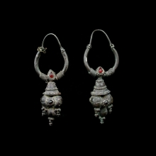 A pair of Gandharan silver earrings with garnet and carnelian inlay