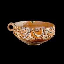 A Persian glazed ceramic bowl with painted designs.