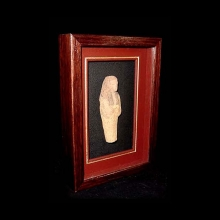 A pottery ushabti with traces of yellow slip on body and black on wig.