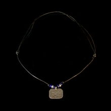 A silver and leather neacklace with egyptian protection amulet in verses from Koran