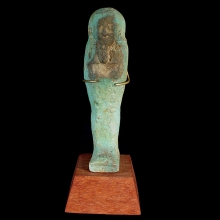 A turquoise-glazed faience ushabti, featuring hieroglyphic text on front panel
