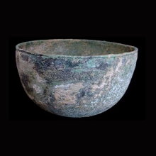 A Western Asiatic bronze vessel of deep form and decorated with stamped motif.