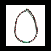 A Zulu trade bead necklace; woven with red, black, white, green glass beads; shell fastener