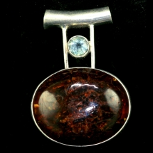 A Baltic amber pendant in sterling silver mount surmounted by a set aquamarine