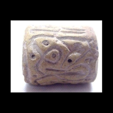 An ancient Indian baked clay cylinder seal with scrolling designs