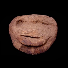 An archaic Dogon stone carving in the form of an animal face with simian features