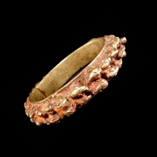 An Indian brass bracelet with raised zoomorphic decoration; remnant red paste