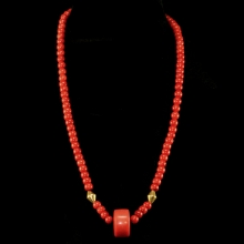 A necklace comprising natural red coral round shaped beads with large central bead and 18 carat gold elements