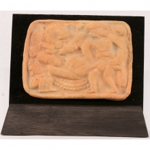 An ancient Indian clay plaque showing an erotic scene with male and female figures and onlooker