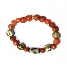 A bracelet comprising carnelian and pumtek beads with a central tiger tooth dzi bead