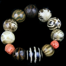 A bracelet comprising round Pumtek beads of various sizes with two Mediterranean natural red round coral beads