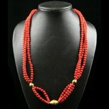 A three tiered necklace comprising Mediterranean (Sardinian) natural red coral round beads with 18 carat gold elements