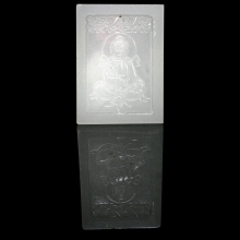 A white Peking glass pendant the front surface with an image of Buddha.