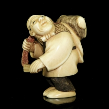Japanese painted ivory Netsuke carving of an actor carrying a mask on his back,  Meiji