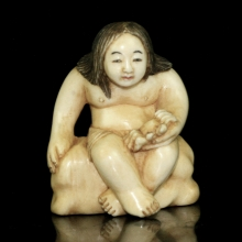 Japanese painted ivory Netsuke carving of a young boy holding a crab,  Meiji