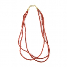 A three tiered necklace comprising Mediterranean (Sardinian) natural red coral round shaped beads with 18 carat gold elements