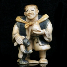 Japanese painted ivory Netsuke carving of an old man with his pet monkey