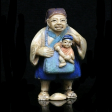 Japanese painted ivory Netsuke carving of a woman holding a baby