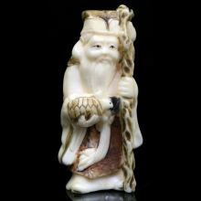 Japanese painted ivory Netsuke carving of a Lohan holding a staff and tortoise.