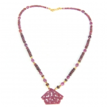 A necklace comprising Indian natural ruby graduated round beads with gold elements and central floral pendant