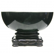 A late Qing Dynasty nephrite spinach jade bowl on hardwood stand