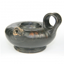 A Greek glazed guttus with lion faced spout