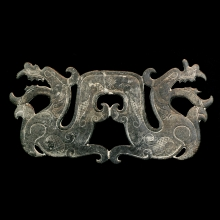 A late Qing to early Republic dark green plaque depicting a double headed dragon