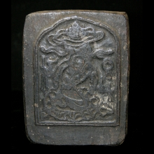 A carved wooden Tibetan ink-block with mythical beast and script.