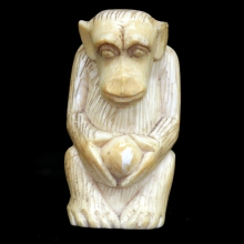 An ivory carving of a seated chimpanzee