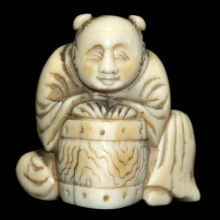 Japanese ivory Netsuke carving of a young boy with a basket, Edo