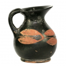 A Xenon ware black glazed oenochoe with painted leaf designs