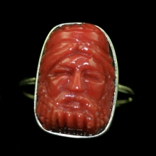 An 18 carat gold ring with carved Sardinian natural red coral bezel carved in figurative form