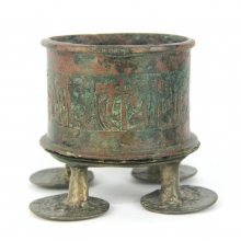 Islamic bronze vessel the outer surface engraved with script, the vessel resting on a circular base with round feet engraved with eyes on the base.