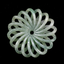 Chinese mottled green jade pendant carved in openwork flower form.