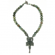 A Mongolian green stone and bronze pendant with pair of eagles.