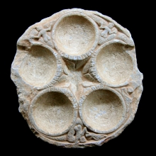 A Gandharan cosmetic palette of grey schist, the five recesses decorated with carved floral and figurative designs.