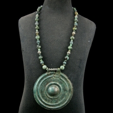 An Islamic bronze and green stone bead necklace with large central bronze discoid pendant